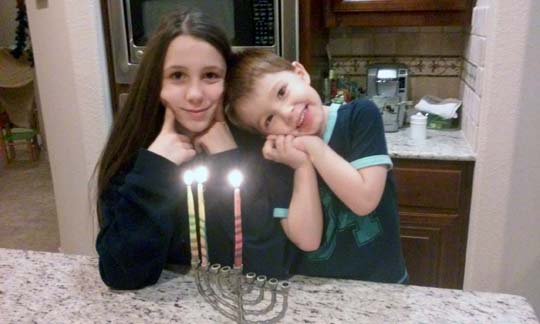 Zach and Grace smile after lighting second candle.