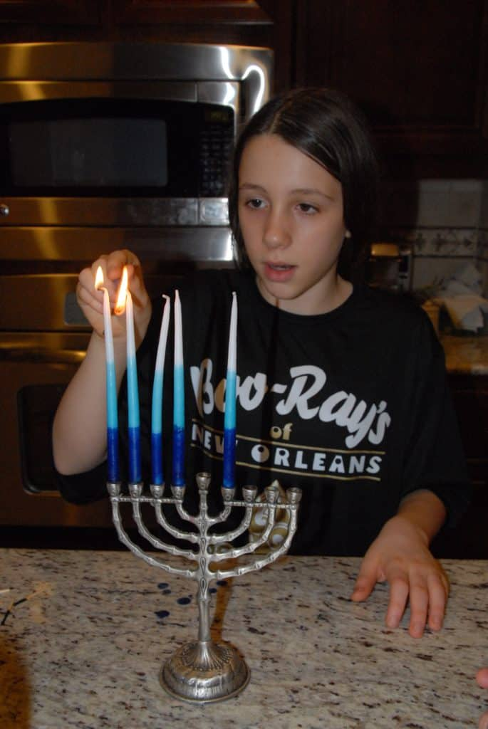 Grace lights candles for Hanukkah.