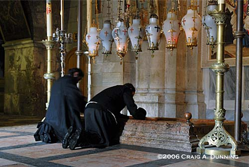 Priests pray at the Thirteenth Station of the Cross: The Stone of Anointment in Jerusalem's Church of the Holy Sepulchre. (Photo: ©2006 Craig A. Dunning)